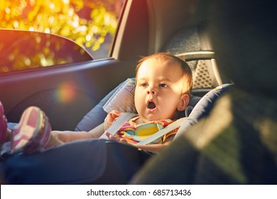 Close Up cute baby sitting in modern car seat. Child new born traveling safety on the road. Safe way to travel fastened seat belts in a vehicle with young kids. Trip with an infant.