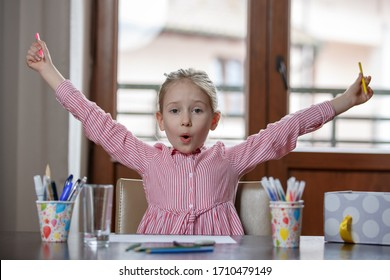 Close up of cute blond hair school girl, sitting at the desk with school supplies, hands raised up, closed at home kid