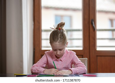 Close up of cute blond hair school girl, sitting at the desk with colored pencils and paper, drawing, closed at home