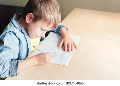 Close up of cute boy doing his homework. Kid writing different lines with pencil. Children education concept.