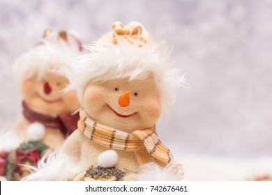close up of a cute Christmas snowman ornament on a winter background.