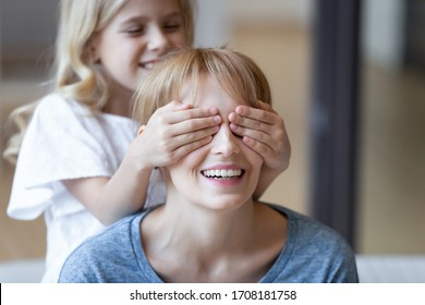 Close up cute daughter making surprise covering eyes to smiling mom on mothers day. Little child girl closing eyes of excited mum preparing present congratulating celebrating happy birthday at home.
