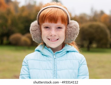 Close up cute ginger girl in the earmuffs smiling, autumn trees behind
