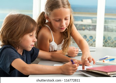 Close up of cute girl helping brother with homework.