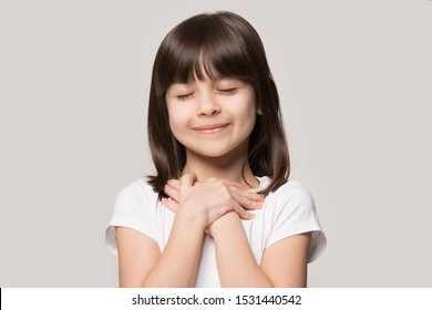 Close up of cute happy small girl isolated on grey studio background hold hands at heart chest feel grateful, smiling little child with eyes closed pray thanking god high powers, faith concept