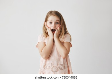 Close up of cute little blond girl with blue eyes in pink t shirt looking in camer, holding hands on cheeks with excited expression.