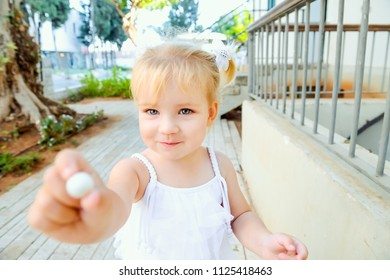 Close up cute little blondy toddler girl in white dress giving small sweet round candy for you. Selective focus. Copy space