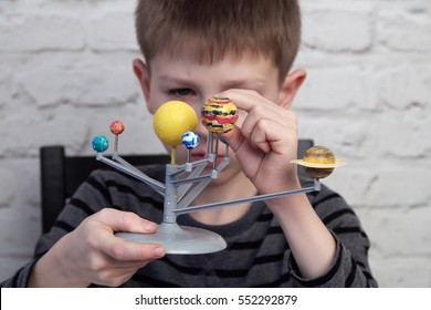 Close up cute little boy is playing with the model of The Solar System