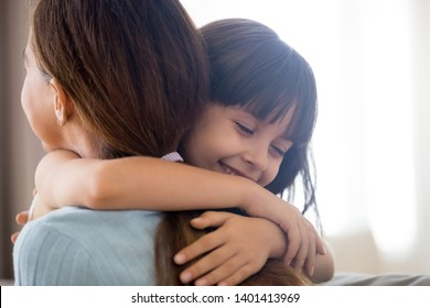 Close up of cute little girl hug young mom or nanny showing love and care, happy preschooler child embrace mother thank or ask forgiveness, smiling parent and small daughter kid cuddle reconcile