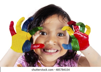 Close up of a cute little girl smiling at the camera with hands painted in colorful