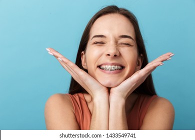 Close up of a cute lovely young girl standing isolated over blue background, grimacing