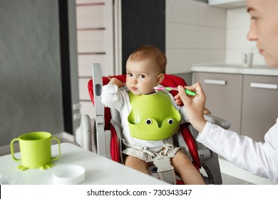 Close up of cute newborn son sitting in kitchen in baby chair and turning head aside refusing to eat baby food. Mother tries to feed him with spoon.
