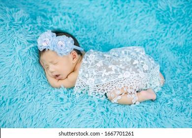 Close up cute Newborn wearing Flower headband on blue wool carpets, fashion concept