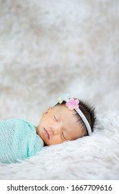 Close up cute Newborn wearing Flower headband on wool carpets, fashion concept