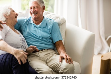 Close up of cute senior couple hugging on sofa