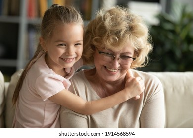 Close up cute smiling little girl hugging mature grandmother, family enjoying tender moment, sitting on cozy couch at home, happy grandma wearing glasses and granddaughter embracing