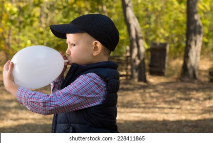 Close up Cute White Male Kid in Black Jacket and Cap Blowing White Balloon Seriously at the Park.