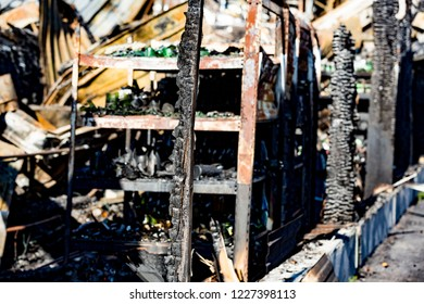 Close up damaged supermarket glass plastic bottles on shelves after arson fire with burn black dark debris waiting for investigation for insurance. Saturated contrasting effect dramatic atmosphere