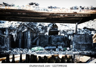Close up damaged supermarket glass plastic bottles after arson fire with burn black dark debris ruins waiting for investigation for insurance. Saturated contrasting effect dramatic atmosphere