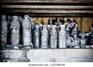 Close up damaged supermarket glass plastic bottles on shelves after arson fire with burn black dark debris  disaster ruins waiting for investigation for insurance. Saturated contrasting effect dramati