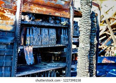 Close up damaged supermarket glass plastic bottles on shelves after arson fire with burn black dark debris ruins waiting for investigation for insurance. Saturated contrasting effect dramatic atmosp