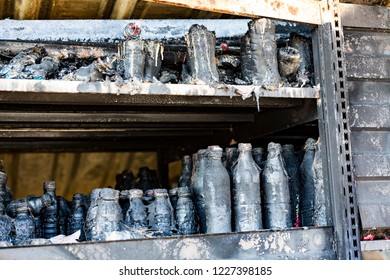 Close up damaged supermarket glass plastic bottles on shelves after arson fire with burn black dark debris  ruins waiting for investigation  insurance. Saturated contrasting effect dramatic atmosphere