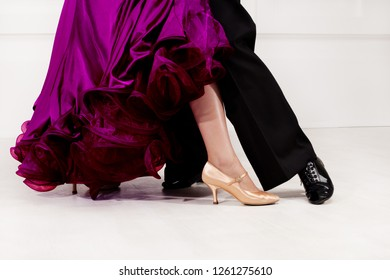 Close up of dancers feet. Ballroom dancers on the dance floor. A man in trousers, a woman in a magnificent ball gown.