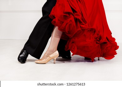 Close up of dancers feet. Ballroom dancers on the dance floor. A man in trousers, a woman in a magnificent ballroom red dress.