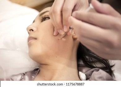 close up danger injection of cosmetic medicine to lifting face with friend.