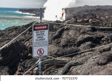 Close up of Danger no trespassing sign that marks safe viewing spot for bright red lava flow of volcano on Hawaii