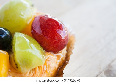 close up danish pastry with fruit on wood table