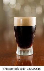 close up of a dark beer on a busy bar top