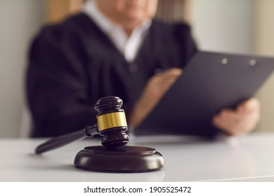 Close up of a dark brown judge's gavel on the table against the background of a judge reading the verdict. Concept of justice, law, jurisprudence and court proceedings. Blurred background.
