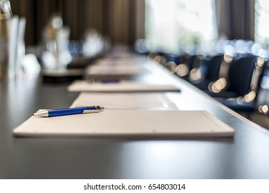 Close up of dark conference table water glasses pens, paper sheets and blurry window background