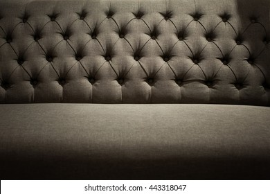 Close up of dark gray fabric backrest sofa in high contrast and dark atmosphere with vintage style.