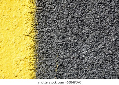 close up of a dark grey asphalt road divided by yellow paint