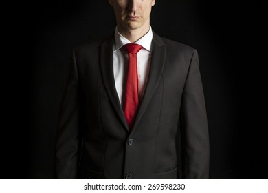 close up dark portrait of an anonymous businessman on black background