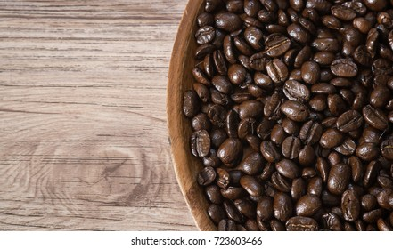 Close up dark roasted Coffee beans on wood palte and on wood background ( Space and composition for text )