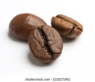 close up of dark roasted fair trade coffee beans on a white background
