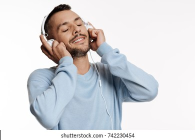 Close up of dark-haired bristled man listening to music