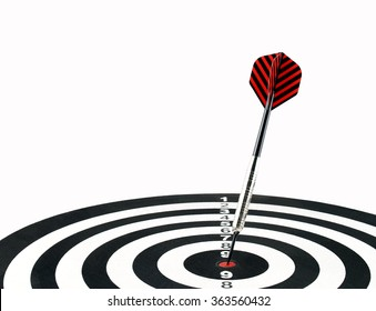 close up dart arrow hitting on target center on bullseye in dartboard isolated on white background, perfection goal success, symbol of aim and achievement