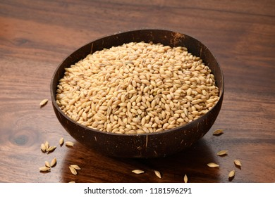 Close up of De hulled Barley in a Earthen Bowl on Wooden Background