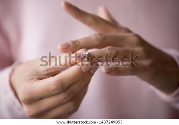 決定的な女性の結婚指輪の接写は夫との別れを決定し、若い女性は離婚や解約の申し立てに問題がある婚約宝石を取り除く