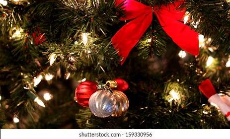 Close up of decorated Christmas tree with ornaments and lights.