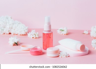 Close up of decorative cosmetic and creams in frame made of lilac flowers on pink background. Beautiful cosmetic set. copyspace