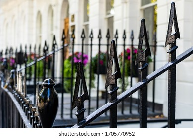 Close up of decorative pointed wrought iron railings in front of Victorian terrace houses in Bloomsbury, London. Brightly coloured flowers bloom in the background.