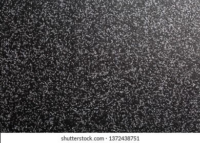 Close up of decorative quartz sand epoxy coated floor or wall coating with grey and black coloured particles. Side lighted
