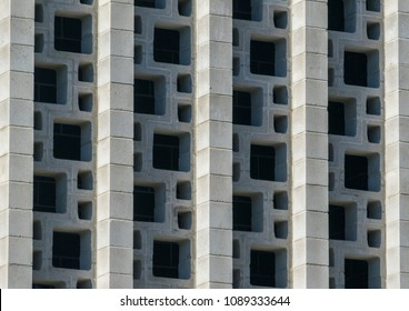 a close up of decorative structural concrete blocks used in the external wall of an office building illuminated by the afternoon sunlight
