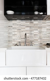 Close up of a deep white kitchen sink and feature tiled splash back