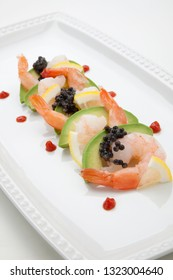 Close up of delicious appetizer shrimp cocktail with black caviar. Garnished with avocado, lemon, and horseradish cocktail sauce for seafood. Elite food.